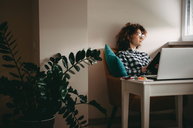 Young businesswoman with curly hair and eyeglasses working from home at the computer thinking about something while holding a book