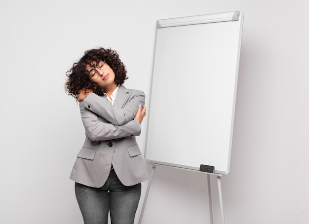 Young businesswoman with curly hair and a white board