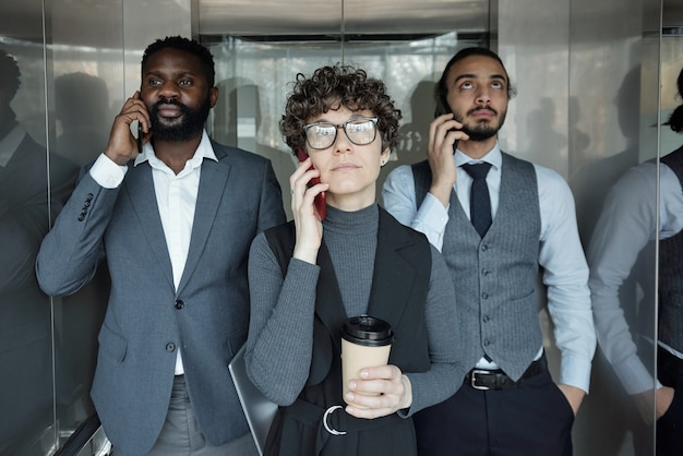 Young businesswoman with glass of coffee and two intercultural male colleagues calling by smartphones in elevator