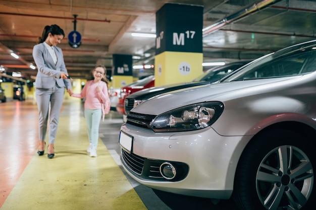 공공 지하 차고에서 그녀의 딸과 함께 젊은 사업가.