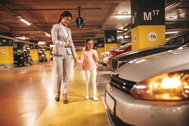 Young businesswoman with her daughter in a public underground garage.