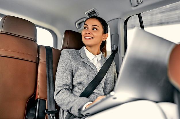 자동차 뒷좌석에 노트북과 젊은 사업가. 럭셔리 자동차에서 일하기 위해 여행하는 여성 임원.