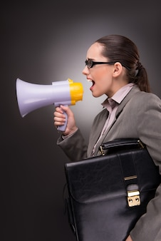 Young businesswoman with loudspeaker in business concept
