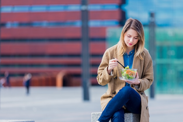 Young businesswoman with salad at urban city outdoor.