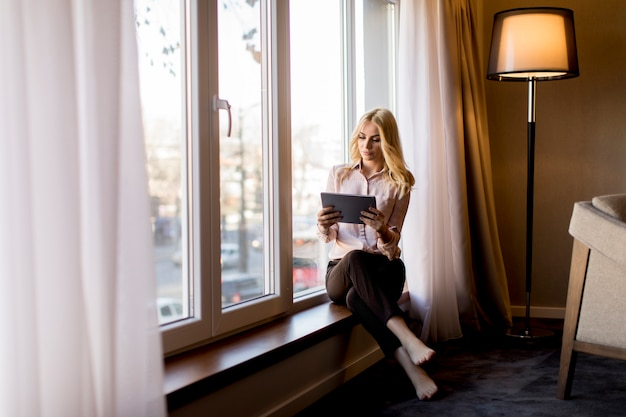 Young businesswoman with tablet sitting by window in the room