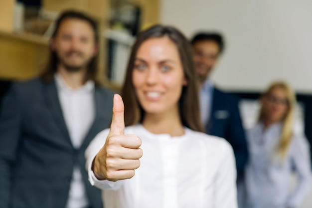 Young businesswoman with thumb up standing in the office