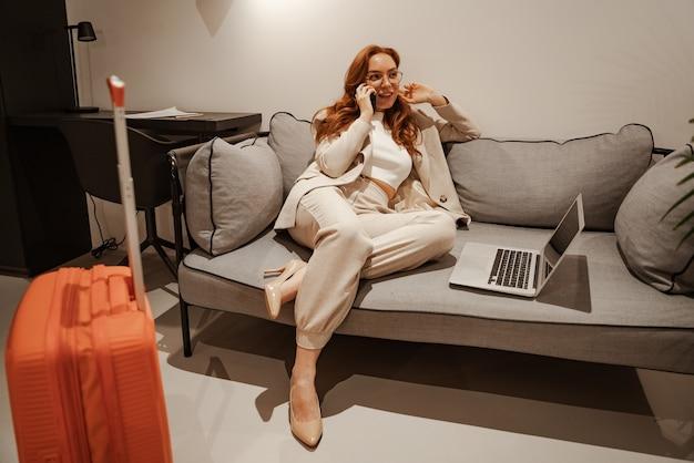 若い実業家はホテルで働いています。出張のコンセプト。スタイリッシュなビジネススーツとオレンジ色のスーツケースを身に着けた非常に忙しい赤毛の女性モデルは、ラップトップで動作し、buの間にスマートフォンで話します