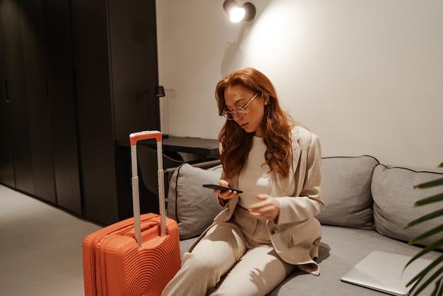 若い実業家はホテルで働いています。出張のコンセプト。スタイリッシュなビジネススーツとオレンジ色のスーツケースを身に着けた非常に忙しい赤毛の女性モデルは、出張中にスマートフォンで動作します。