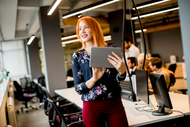 Young businesswoman working on digital tablet while in the background team working in the modern office