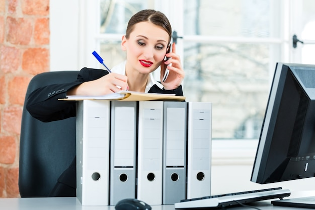 Молодой предприниматель, работающий в своем офисе, сидит за папками и разговаривает по телефону с клиентом или клиентом