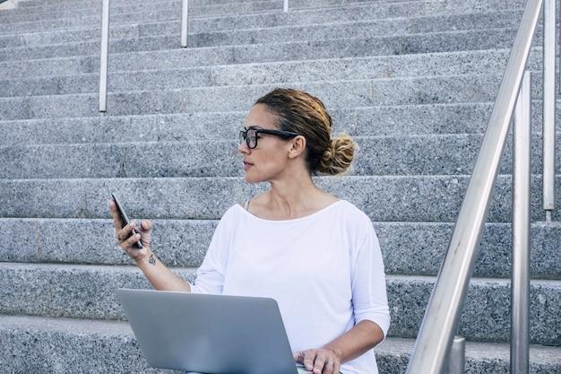 屋外の階段に座ってラップトップに取り組んでいる若い実業家。ステップでラップトップを使用しながら携帯電話で白人女性のテキストメッセージング。働いて、モバイルを使用して幸せな女性。