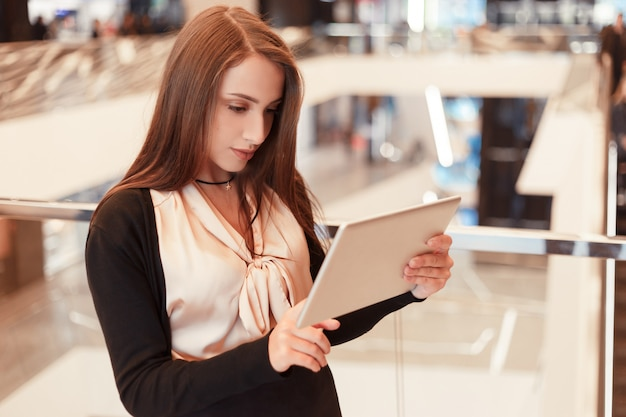 Young businesswoman working using an electronic tablet standing in a modern office