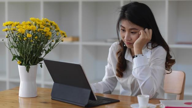 事務室で彼女の手で彼女のあごを休ませながらタブレットで作業している若い実業家