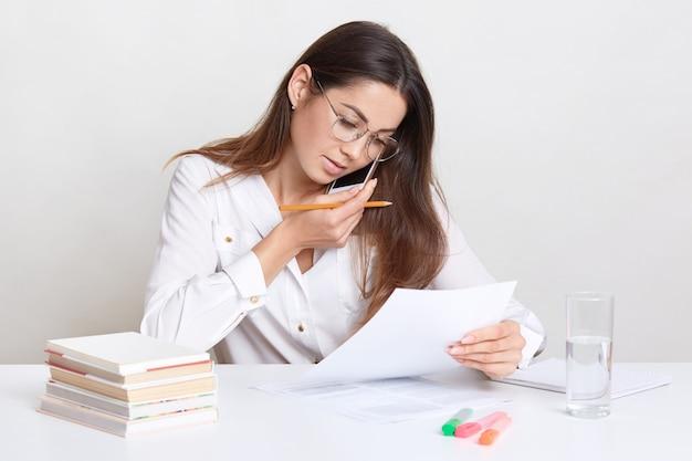 若い実業家がリモートで作業し、携帯電話で話し、銀行の残高を確認し、鉛筆を握り、文書を検証し、科学論文を使ってコース用紙を書き、フォーマルな服を着ている