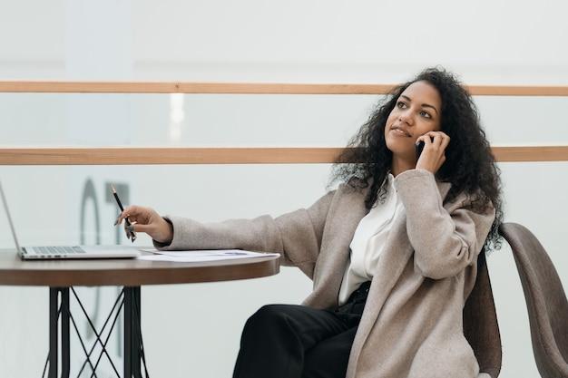 Молодой предприниматель работает, сидя за столом в фуд-корте