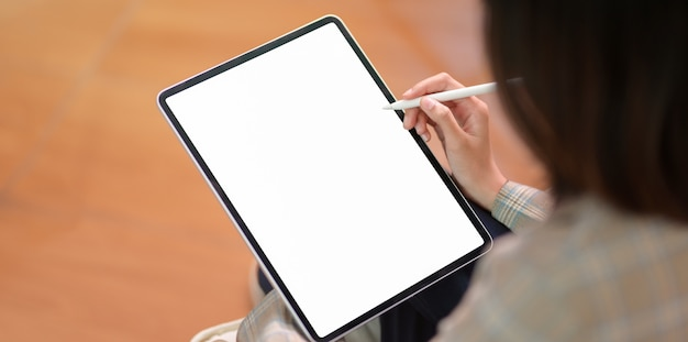 Young businesswoman writing on blank screen tablet