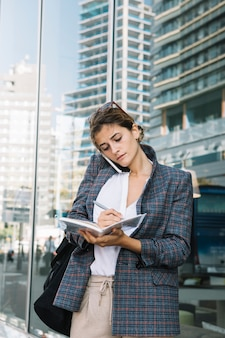 Young businesswoman writing notes in the notebook with pen standing against reflective glass