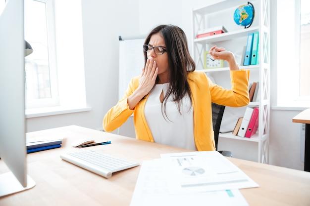 Молодой предприниматель, зевая в офисе