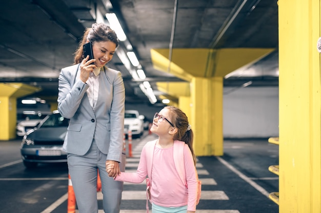 젊은 여성 사업가가 전화 통화를 하고 공공 지하 차고에서 딸과 함께 걷고 있습니다.