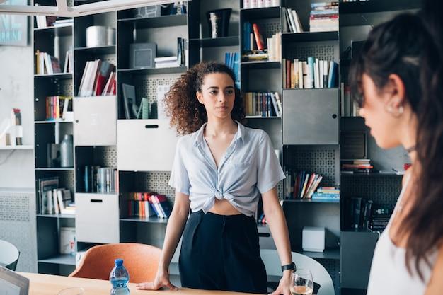 Young businesswomen having informal meeting in modern co-working office