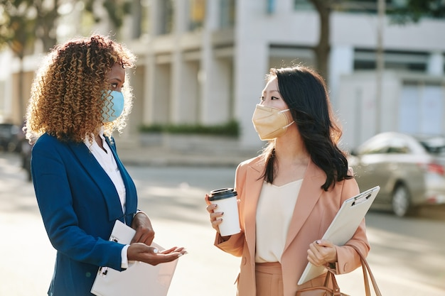 Young businesswomen in protective masks drinking take away coffee and discussing project when standing in the street