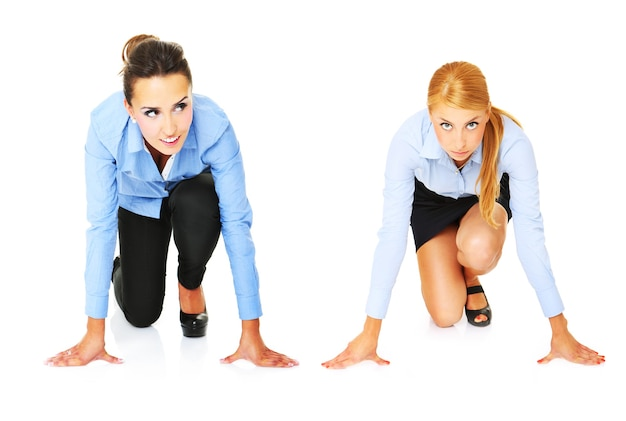 Young businesswomen ready to start a race over white background