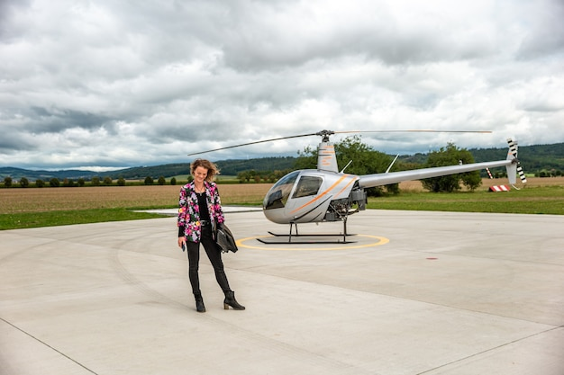 A young busineswoman at a private airport is waiting for a helicopter departure