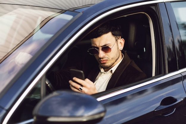 Young bussinesman in suit and black glasses speaks by phone in his car. bussines look. test drive of the new car