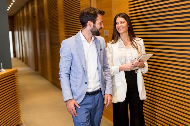 Молодая бизнес-пара в офисе Premium Фотографии