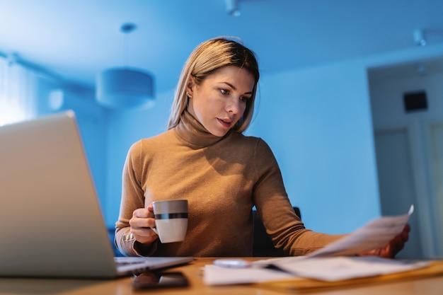 Молодая занятая блондинка-фрилансер сидит дома, держит документы и кофе и работает над важным проектом