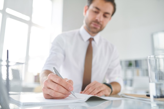コピーブックの空白のページにペンを置いてノートを作ろうとする若い忙しいブローカー