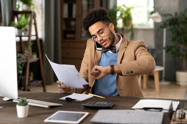 Молодой занятый бизнесмен сидит на своем рабочем месте, работает с документами и разговаривает по мобильному телефону в течение рабочего дня в офисе