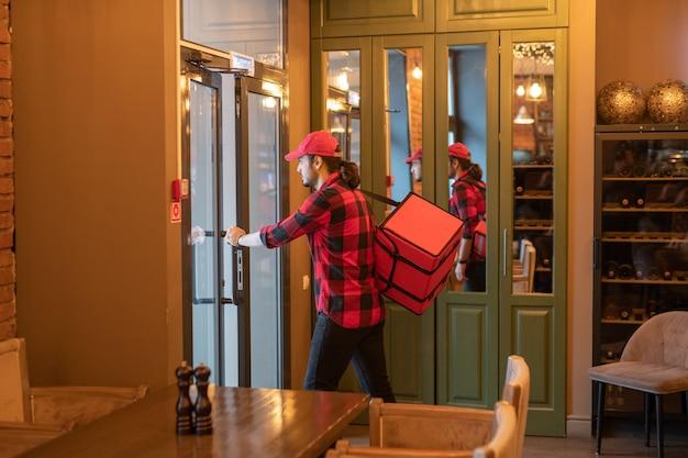 現代的な上品なレストランのクライアントに注文を届ける間、ドアを開ける大きな赤いバッグを持つ若い忙しい宅配便