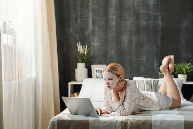 彼女の顔の世話をし、在宅勤務中にラップトップの前のベッドに横たわっているシルクのパジャマで忙しい若い女性
