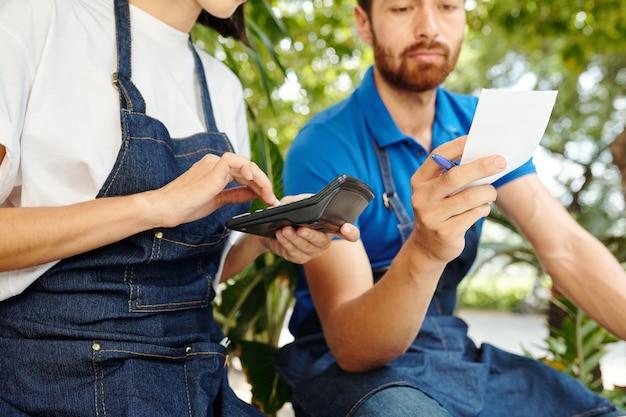 Молодые владельцы кафе сидят на улице и рассчитывают средний чек с продаж