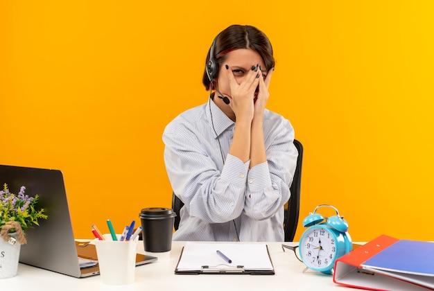 오렌지 배경에 고립 된 손가락을 통해 카메라를보고 손으로 얼굴을 덮고 작업 도구로 책상에 앉아 헤드셋을 착용하는 젊은 콜 센터 소녀