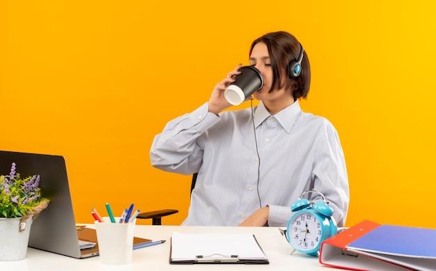 오렌지 배경에 고립 된 닫힌 된 눈을 가진 플라스틱 커피 컵에서 커피를 마시는 작업 도구와 책상에 앉아 헤드셋을 착용하는 젊은 콜 센터 소녀