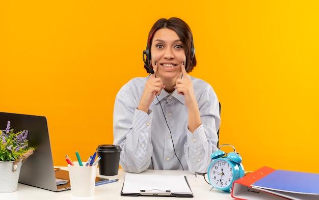 オレンジ色の背景に分離されたカメラを見て笑顔を偽って作業ツールと机に座っているヘッドセットを身に着けている若いコールセンターの女の子