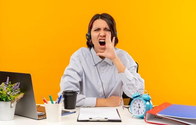 오렌지 배경에 고립 된 닫힌 눈으로 큰 소리로 외치는 입 근처에 손을 넣어 작업 도구와 책상에 앉아 헤드셋을 착용하는 젊은 콜 센터 소녀