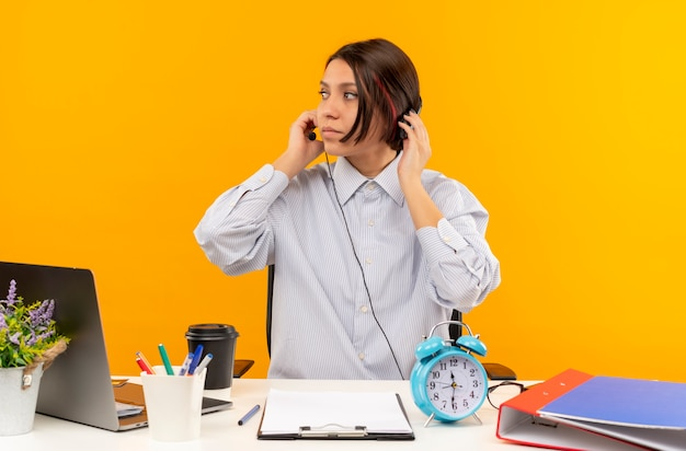 Giovane ragazza del call center che indossa la cuffia avricolare che si siede allo scrittorio con gli strumenti di lavoro che mettono le mani sull'auricolare che esamina il lato isolato su fondo arancio