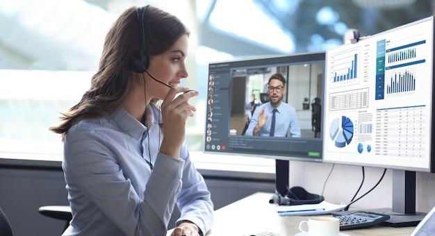 Молодая женщина call-центра, работающая на компьютере, делает видеоконференцию с коллегами на пк. обсуждение финансового отчета своей компании. дистанционная работа. коронавирус.