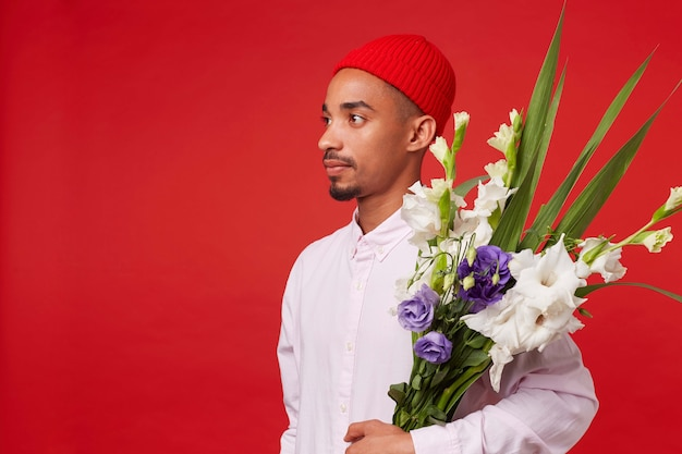 Young calm african american guy in white shirt and red hat, looks away and holds bouquet , stands over red background.