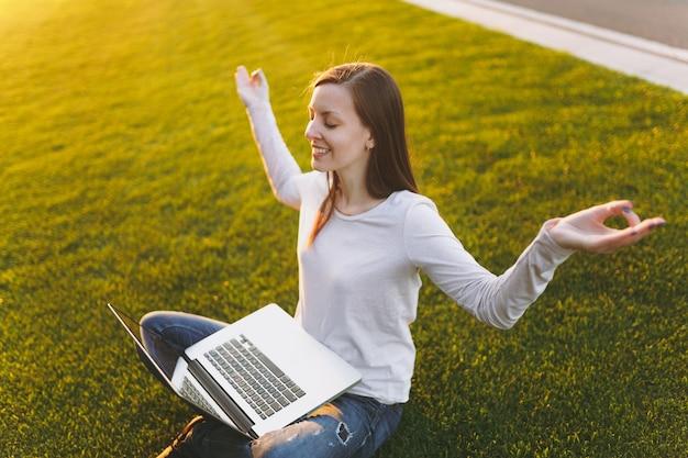 カジュアルな服装の若い穏やかな学生女性。座って、リラックスして、ヨガのジェスチャーで手を振る女性。屋外の緑の芝生の地面の日光の芝生の上のラップトップpcコンピュータ。モバイルオフィス。フリーランスのビジネスコンセプト。