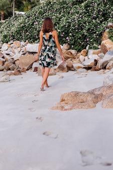 Молодая спокойная татуированная женщина в летнем коротком платье с тропическим принтом на скалистом пляже с зеленым кустом и фиолетовыми розовыми цветами