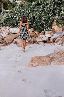 緑の茂みと紫のピンクの花と岩のビーチで夏の熱帯プリントショートドレスの若い穏やかな入れ墨の女性