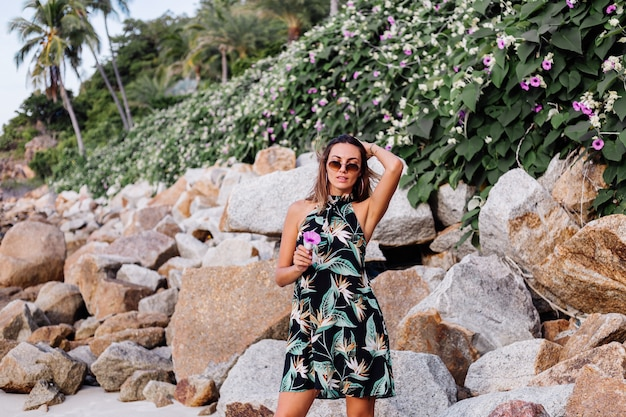 Young calm tattooed woman in summer tropical print short dress on rocky beach with green bush and purple pink flowers