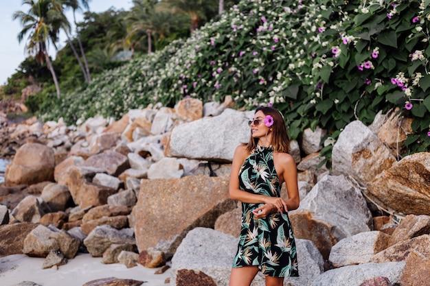 Giovane donna tatuata calma in abito corto stampa estiva tropicale sulla spiaggia rocciosa con cespuglio verde e fiori rosa viola