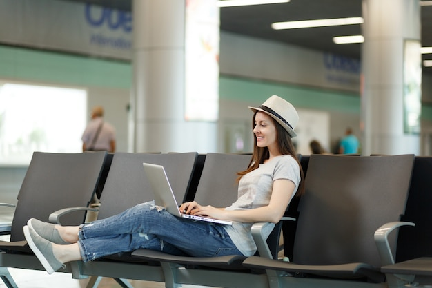 国際空港のロビーホールで待っている間ラップトップに取り組んで帽子の若い穏やかな旅行者観光客の女性