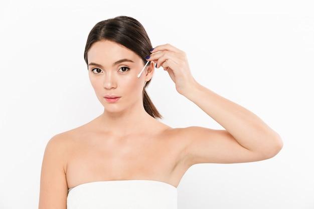 白で分離された顔をきれいに綿棒を使用して若い穏やかな女性