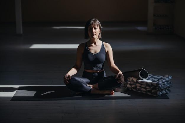 Young calm yogi woman in easy yoga pose. yoga studio interior.